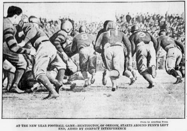 """Photograph from a football game between Oregon and Pennsylvania teams, published in the Evening Public Ledger of Philadephia, Pennsylvania on January 10, 1917. Caption reads: """"At the new year football game - Huntington, of Oregon, starts around Penn's left end, aided by compact interference."""""""