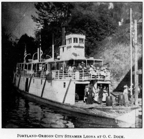 """Photograph of a steamboat with several passengers aboard has caption that reads: """"Portland - Oregon City Steamer Leona at O.C. Dock"""""""
