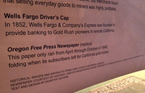"""Hanging sign next to the exhibit explains each of the artifacts on display. Photo shows a closeup of the description for the Wells Fargo driver's cap: """"In 1852, Wells Fargo and Company's Express was founded to provide banking to Gold Rush pioneers in remote California,"""" and descriotion of the Oregon Free Press newspaper (replica): """"This paper only ran from April through November of 1848, folding when its subscribers left for California gold mines."""" Credits at the bootom read: """"Historical images and artifacts from Lane County HIstorical Museum, Newspaper courtesy of Historic Oregon Newspapers online, University of Oregon Libraries' Oregon Digital Newspaper Program, Text and Design by Dorothy Bayern."""""""
