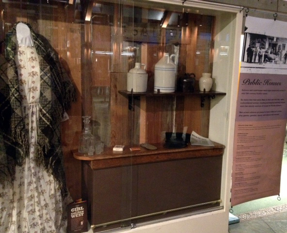 Photograph of the exhibit shows a woman's dress and shawl from the 1850s, a crystal decanter and glasses, antique ceramic jugs, a tobacco storage container, rolling papers, and other items from the Gold Rush time period.