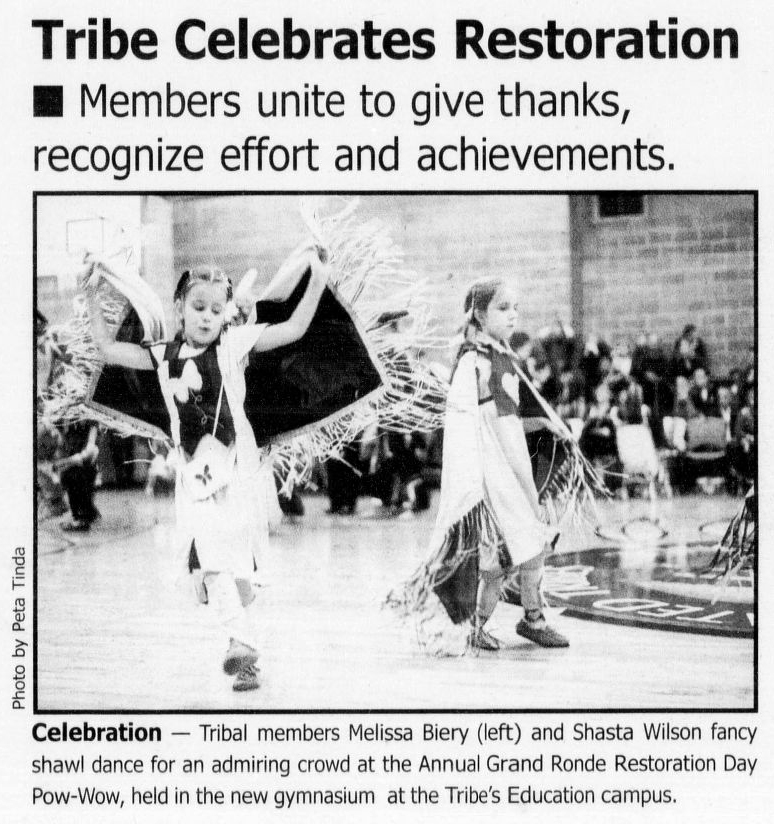 "Clipping shows an image of two children in traditional regalia, dancing inside a gymnasium. Clipping reads: ""Tribe Celebrates Restoration. Members unite to give thanks, recognize effort and achievements. Celebration - Tribal members Melissa Biery (left) and Shasta Wilson fancy shawl dance for an admiring crowd at the Annual Grand Ronde Restoration Day Pow-Wow, held in the new gymnasium at the Tribe's Education campus."""