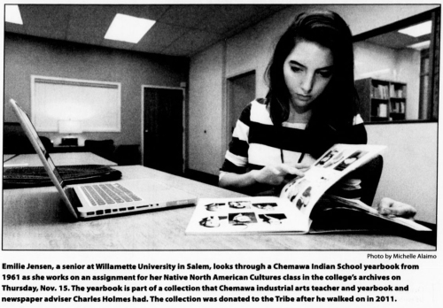"Image shows a student with a yearbook and laptop, working at a desk. Caption reads: ""Emilie Jensen, a senior at Willamette University in Salem, looks through a Chemawa Indian School yearbook from 1961 as she works on an assignment for her Native North American Cultures class in the college's archives on Thurs. Nov. 15. The yearbook is part of a collection that Chemawa industrial arts teacher and yearbook and newspaper advisor Charles Holmes had. The collection was donated to the Tribes after he walked on in 2011."