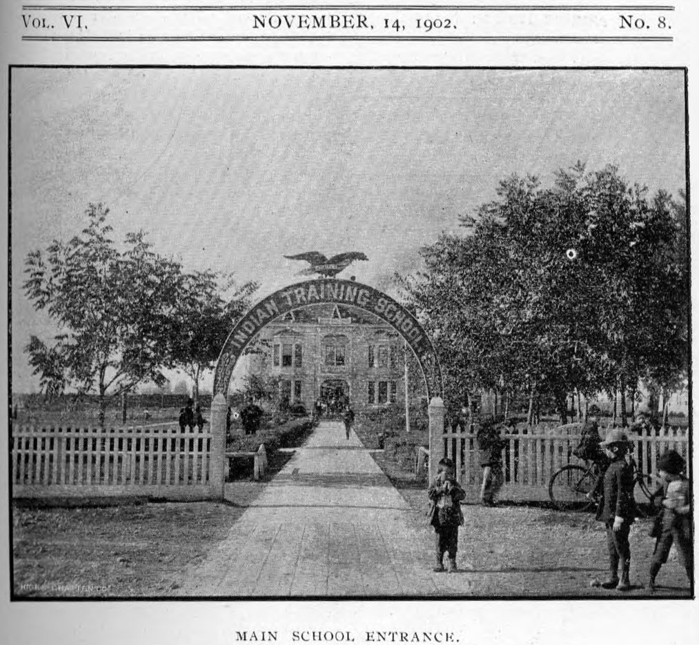 "Image from the Weekly Chemawa American shows a fence and gate with a sign that says ""Indian Training School"" surrounding a yard with two trees and a building in the distance. Children are standing around the scene, with one child on a bicycle. Image is on the front page of Vol. 6 issue 8, dated November 14, 1902. Caption reads ""Main school entrance."""