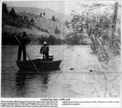 "Photograph of two men in a boat on a river. Caption reads: ""Gathering data chilly job. Warm Springs tribal biologist Mark Fritsch and John Ogan from the Oregon Dept. of Fish and Wildlife brave the cold while they collect data. By taking an inventory of native fall chinook carcasses tagged earlier in the year at Sherar's Falls, biologists are able to make population estimates."